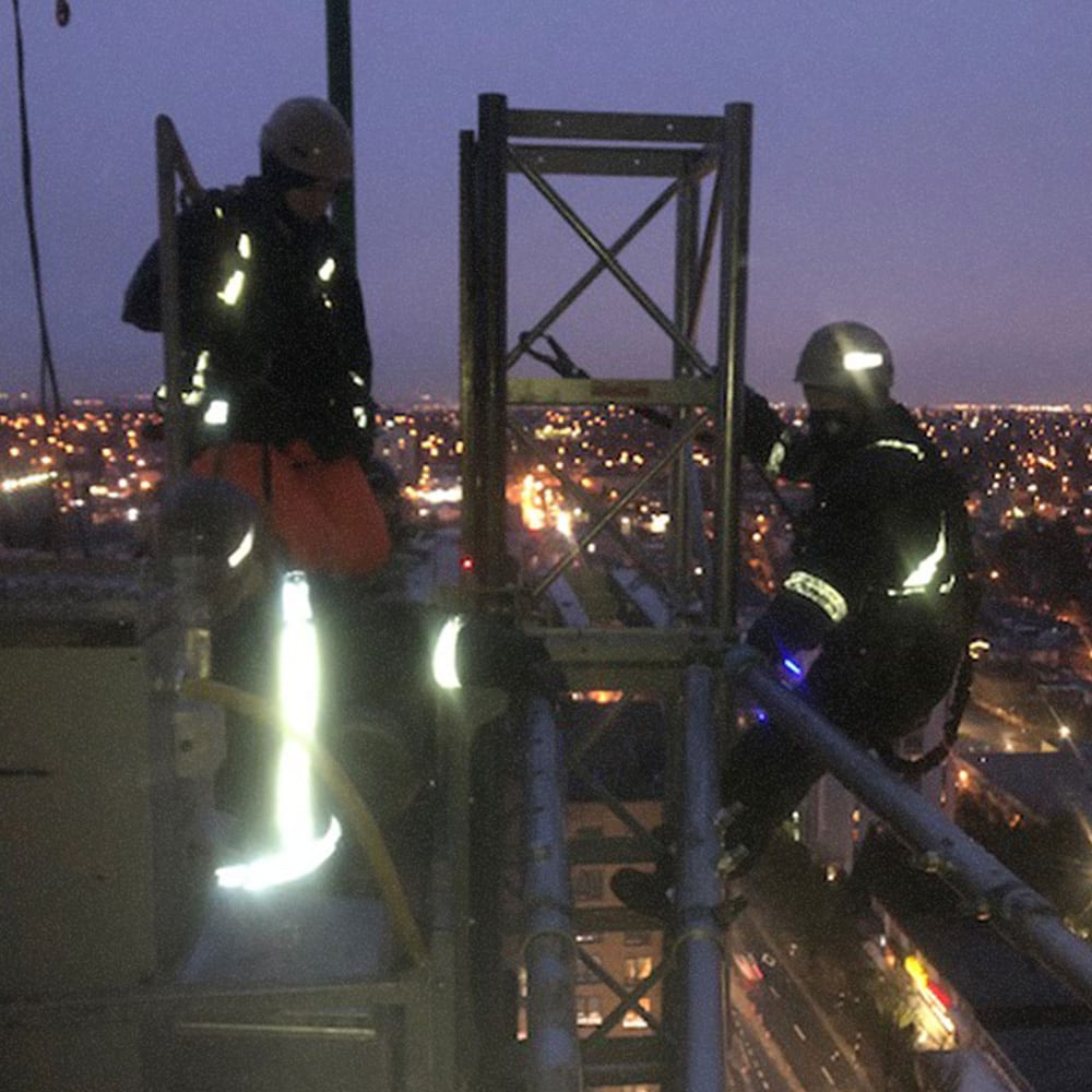 Two men setting tie-backs at the top of a tower