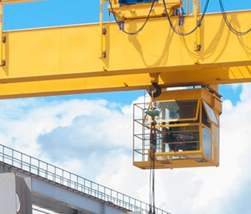 Zoomed in image of overhead crane operator working in the sky.